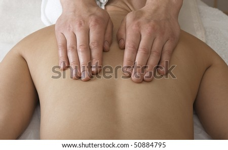 Woman is getting back massage from a physiotherapist. - stock photo