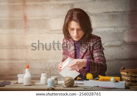 Woman is handcrafting a decorative house - stock photo