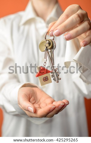 woman is handing a house key. Key with a key-chain in the shape of house