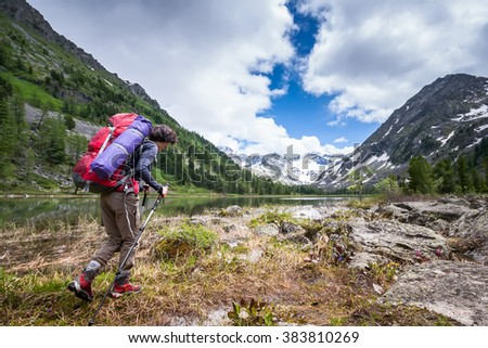 Woman is hiking on trail at the lake in mountains of Altai