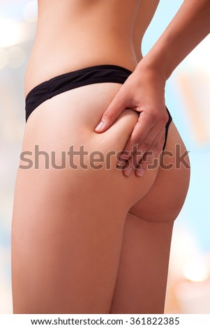 Woman is holding a bit of fats on her butt. Image isolated with work path. - stock photo