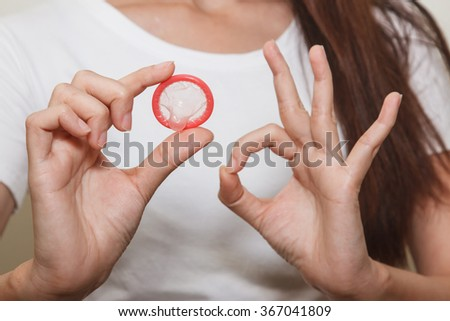 Woman is holding a condom - stock photo