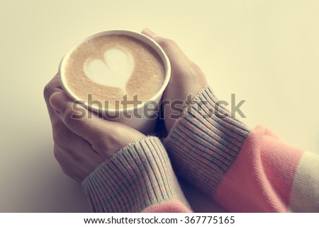 Woman is holding a cup of coffee vintage colors - stock photo