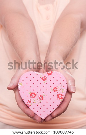 Woman is holding a cute pink heart in her hands - stock photo