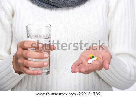 Woman is holding a glass of water and tablets in hands. On the white background. - stock photo