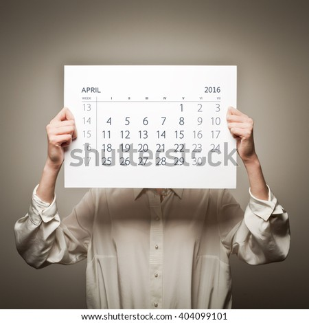 Woman is holding April calendar of the year two thousand sixteen.