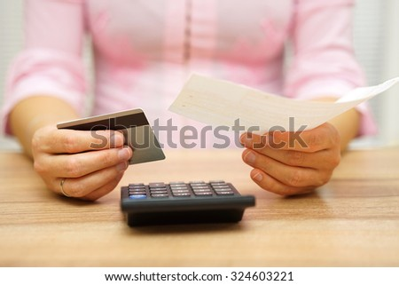 woman is holding bill and credit card in hands  and calculating the costs - stock photo