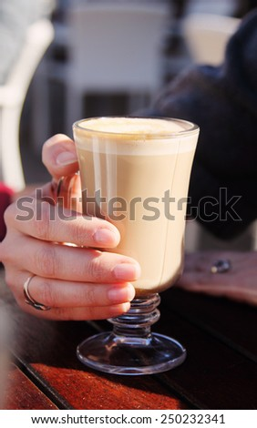 woman is holding cup of coffee cappuccino - stock photo