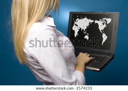 Woman is holding laptop with world map on the screen. - stock photo