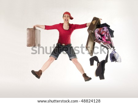 Woman is holding suitcase and  jumping.