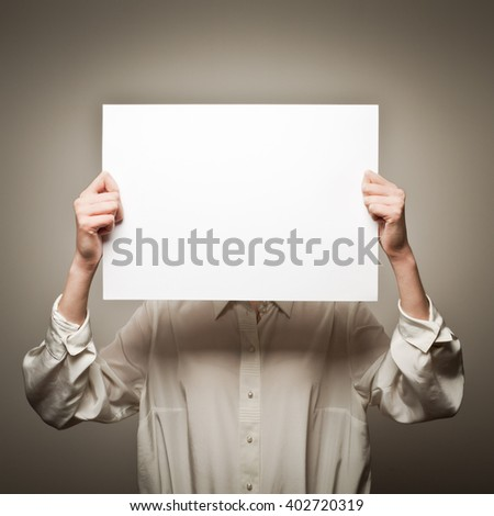 Woman is holding white paper in her hands - stock photo