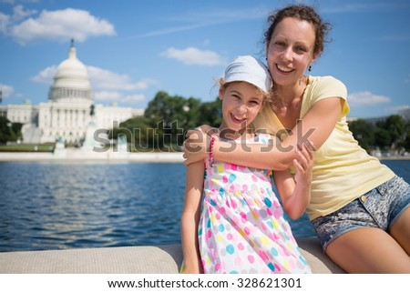 Woman is hugging her daughter near pond and Capitol at summer. - stock photo
