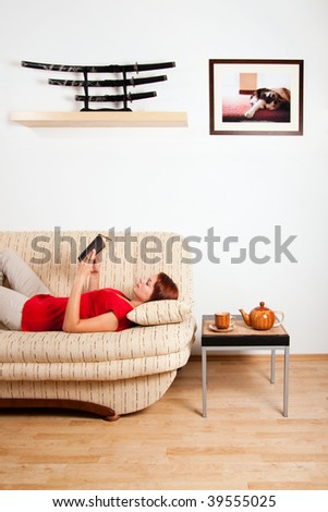 Woman is lying on a sofa at home and reading a book. Image on the wall was photographed by me. - stock photo