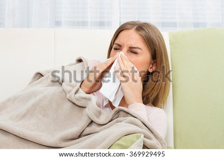 Woman is lying on sofa and blowing nose.Woman having flu