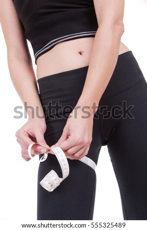 Woman is measuring her leg isolated on white background