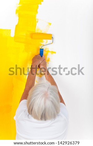 Woman is painting with a roller in yellow color - stock photo