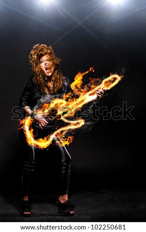 woman is playing rock music on fiery guitar - stock photo