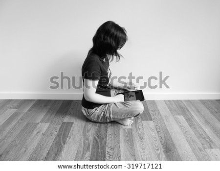 woman is playing tablet and watching picture in there, black and white image