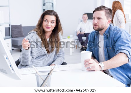 Woman is pointing something out on a screen to her co-worker