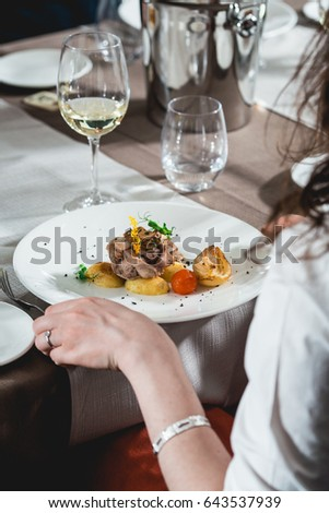 woman is preparing to eat delicious roulade of rabbit meat in a restaurant. small portion.