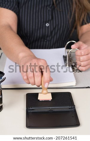 Woman is pressing a stamp at a stamp pad at the desk.