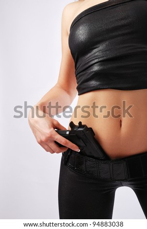 Woman is pushing a handgun into her skintight pants. She is wearing a black leather top and trousers. Only left arm and left part of her sexy body are in sight. There is copy space. - stock photo