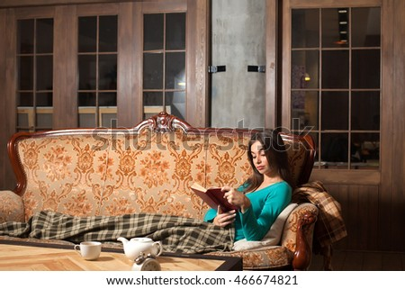 Woman is reading a red book on the sofa with 