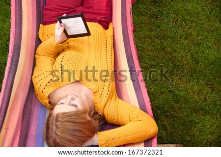 woman is reading the e-book lying on the hammock - stock photo