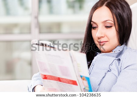 woman is relaxing at home while reading a magazine