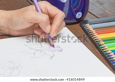 Woman is relaxing by drawing a lily flowers with a purple  pencil on white paper. On the wooden table is ready set of multicolored crayons in a box. - stock photo