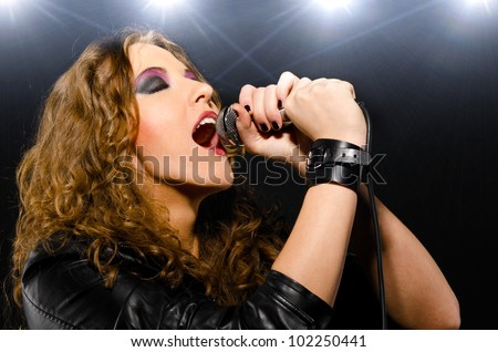woman is singing rock song with a microphone - stock photo