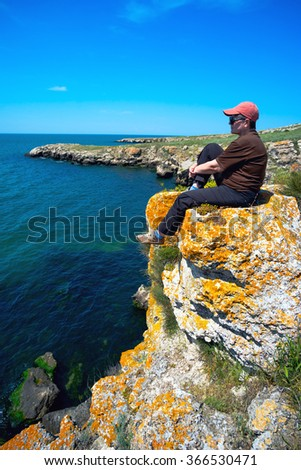 woman is sitting around on the steep shore of the sea of Azov in the Crimea.