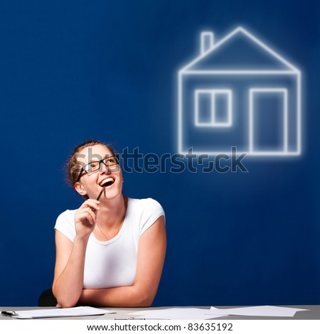 woman is sitting at table and thinking about a house - stock photo