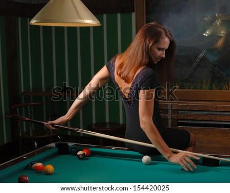 Woman is sitting on the edge of a billiard-table. She is aiming a cue from her back. - stock photo