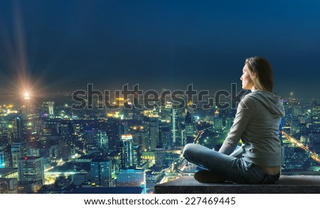 Woman is sitting over the city - stock photo