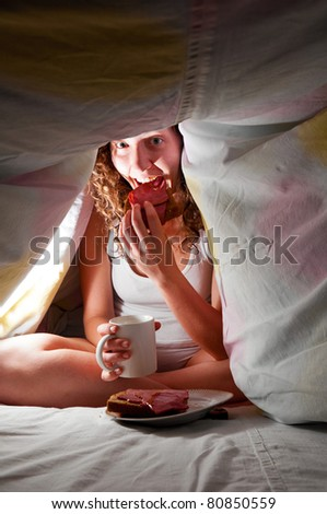 woman is sitting under cover in bed and eating - stock photo