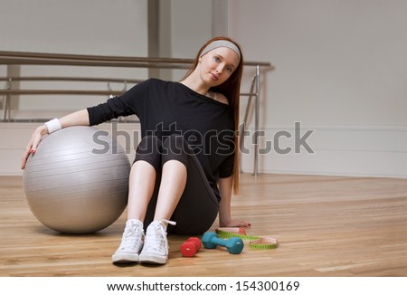 Woman is sitting with fitness ball, weights and measure
