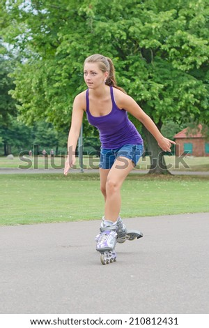 Woman is skating rollerblades in the park. - stock photo
