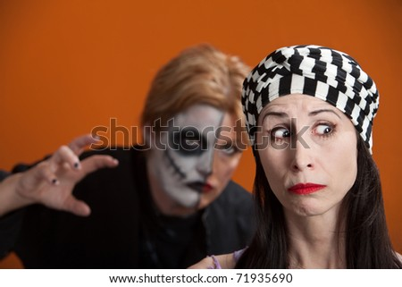 Woman is stalked by another in scary makeup - stock photo