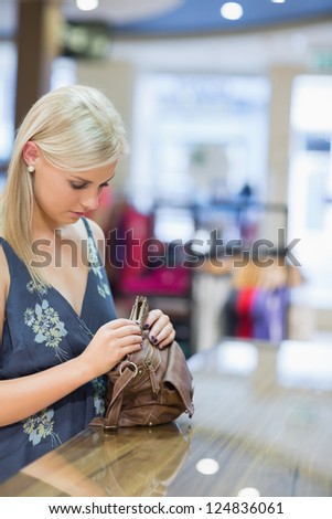 Woman is standing at the counter of the shop while searching in her bag - stock photo