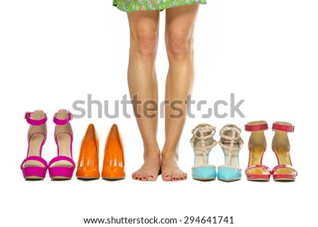 Woman is standing barefoot in between high heels shoes - stock photo
