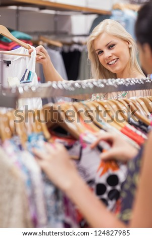 Woman is standing behind a clothes rack of a boutique showing clothes - stock photo