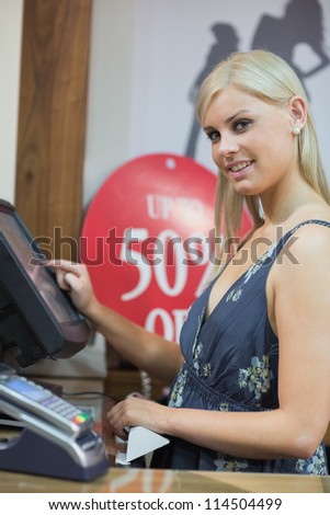 Woman is standing behind counter while typing at the till - stock photo