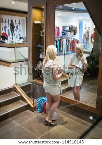 Woman is standing in front of the mirror at the boutique - stock photo