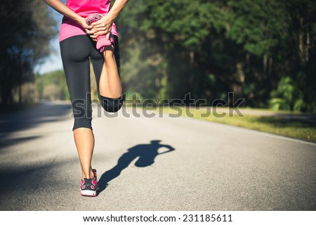 Woman is stretching before jogging. Fitness and lifestyle concept. - stock photo