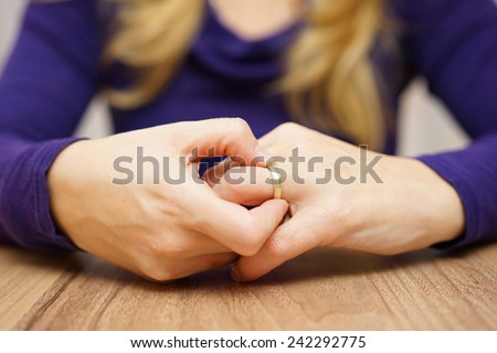 woman is taking off the wedding ring - stock photo