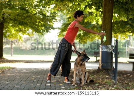 Woman is throwing away the poo of her dog - stock photo