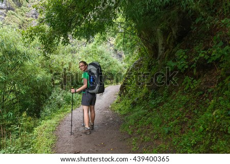 Woman is trekking in tropic forest of Nepal
