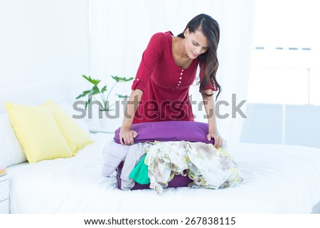 Woman is trying to close her suitcase on the bed - stock photo