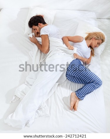 Woman is trying to fall asleep while man is taking most of the blanket in bed.